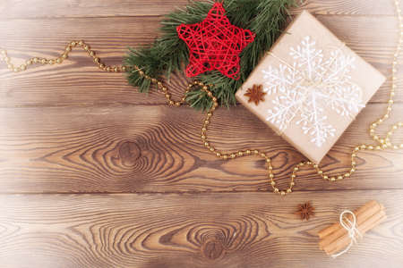Christmas and New Year holiday background. Decor with gifts, fir branches, cones, star, beads, snowflakes, cinnamon sticks on a wooden table. Flat lay, empty space Archivio Fotografico