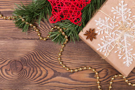 Christmas and New Year holiday background. Decor with gifts, fir branches, cones, star, beads, snowflakes on a wooden table. Flat lay, empty space Archivio Fotografico
