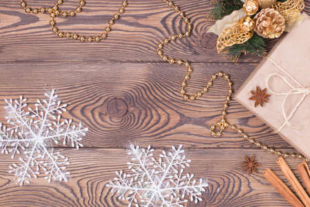 Christmas and New Year holiday background. Decor with gifts, fir branches, cones, Christmas decorations, beads, snowflakes, cinnamon sticks on a wooden table. Flat lay, empty space