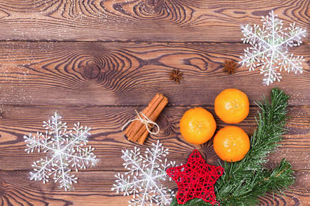 Christmas background - fir branches, pine cone, snowflakes and tangerines, New Year's decor on a wooden table. Flat lay, copy space.