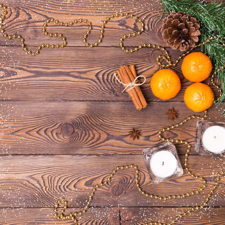 Christmas background - fir branches with cones, tangerines with cinnamon, star anise, candles, Christmas decor. Flat lay, empty space