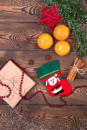 Red stocking with fir branches, gift wrapped in kraft paper, tangerines, cinnamon sticks and Christmas decorations on a wooden table. Top view, vertical photo, copy space. Archivio Fotografico