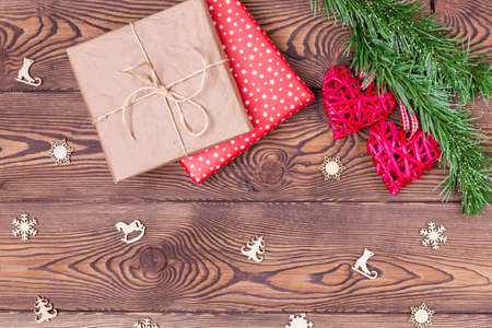 Christmas decor or background for Valentine's Day. Two red hearts from rattan on a spruce branch and a gift wrapped in paper on a wooden table. Top view, copy space.