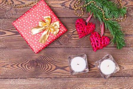 Christmas decor or background for Valentine's Day. Two red hearts from rattan on a spruce branch and a gift wrapped in paper and candles on a wooden table. Top view, copy space