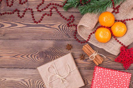 Christmas composition with tangerines, cinnamon, star anise, gifts wrapped in paper and fir branches, New Year's decor on a wooden background. Flat lay, copy space.