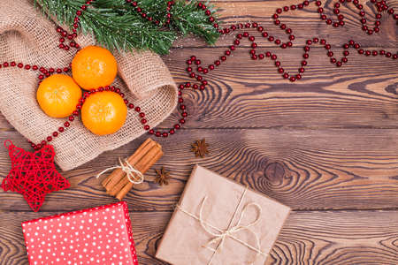 Christmas composition with tangerines, cinnamon, star anise, gifts wrapped in paper and fir branches, New Year's decor on a wooden background. Top view, copy space.