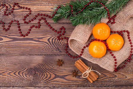 Christmas composition with tangerines, cinnamon, star anise and fir branches, New Year's decor on a wooden background. Top view, copy space. Archivio Fotografico
