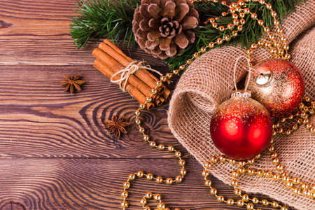 Christmas composition, red balls and gold beads, cinnamon, star anise, fir branches, New Year's decor on a wooden background. Flat lay, copy space.
