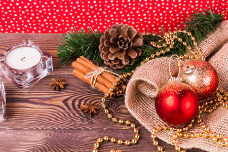New Year's composition, red balls and golden beads, cinnamon, star anise, fir branches, candles, New Year's decor on a wooden background