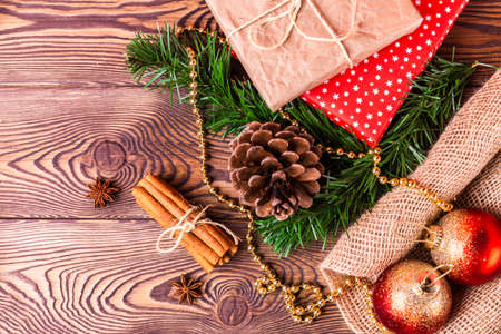 Christmas and New Year holiday background. Decor with fir branches, cones, Christmas decorations, beads, a gift wrapped in paper, cinnamon sticks on a wooden table. Flat lay
