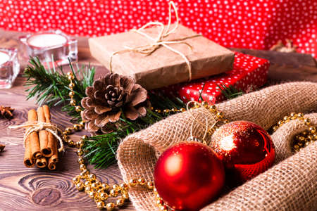 Christmas and New Year holiday background. Decor with fir branches, cones, Christmas decorations, beads, a gift wrapped in paper, cinnamon sticks, candles on a wooden table.