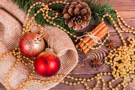 Christmas composition, red balls and gold beads, cinnamon, star anise, fir branches, New Year's decor on a wooden background