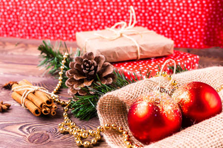 Christmas and New Year holiday background. Decor with fir branches, cones, Christmas decorations, beads, a gift wrapped in paper, cinnamon sticks on a wooden table Archivio Fotografico