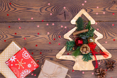 Metallic golden fir tree with branches and cones, Christmas decorations, beads and gifts wrapped in paper on a wooden table. Flat lay, copy space