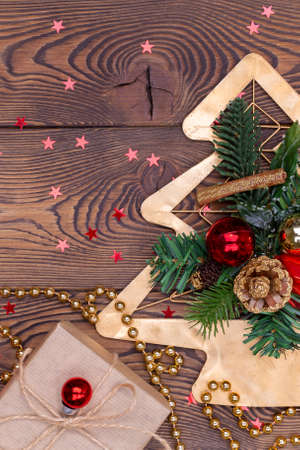 Metal golden Christmas tree with branches and cones, Christmas decorations, beads and gifts wrapped in paper on a wooden table. Vertical photo, top view, copy space