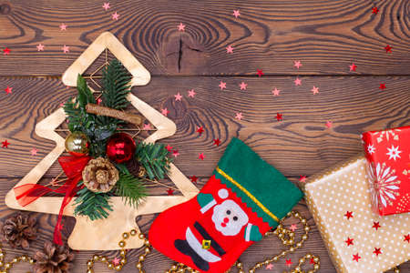 Red felt stocking and metallic golden fir tree with branches and cones, Christmas decorations, beads and gifts wrapped in paper on a wooden table. Top view, copy space