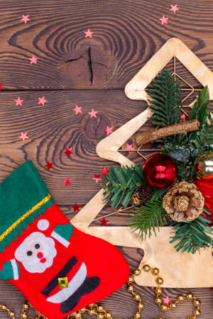 Red felt stocking with fir branches and Christmas decorations, snowflakes, beads on a wooden table. Top view, copy space, Vertical photo. Archivio Fotografico