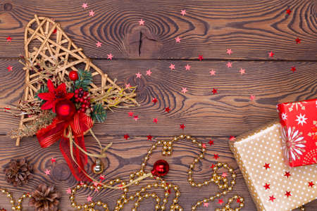 Golden bell from ratang with branches and cones, Christmas decorations, shiny beads and gifts wrapped in paper on a wooden table. Top view, copy space. Archivio Fotografico