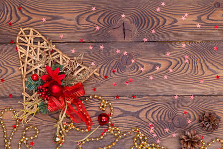 Golden bell from rattan with pine cones, Christmas toys, shiny beads and small red shiny stars on a wooden table. Top view, copy space.