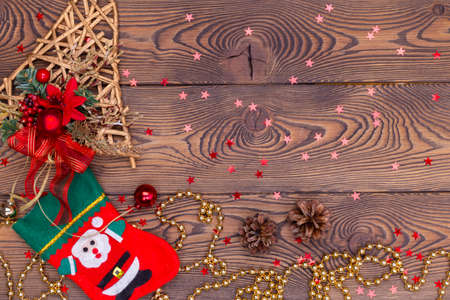 Red felt stocking with the image of Santa, a golden ratang bell with Christmas decorations, pine cones, snowflakes, shiny beads on a wooden table. Top view, copy space