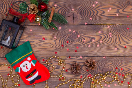 Red stocking with fir branches and Christmas decorations, snowflakes, beads on a wooden table. Top view, copy space.