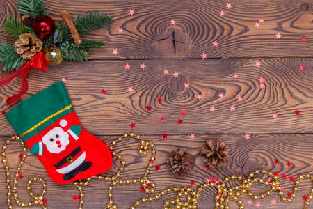 Red felt stocking with the image of Santa, fir branches, cones and Christmas decorations, snowflakes, beads on a wooden table. Top view, copy space.