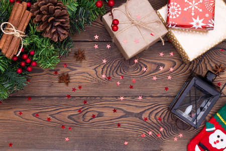 Christmas or new year background, composition of christmas decorations and fir branches, gifts wrapped in paper, candles, flat lay, empty space for greeting text