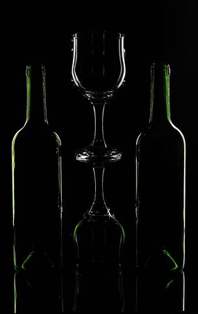 Wine bottle and wine glasses on a black background photo
