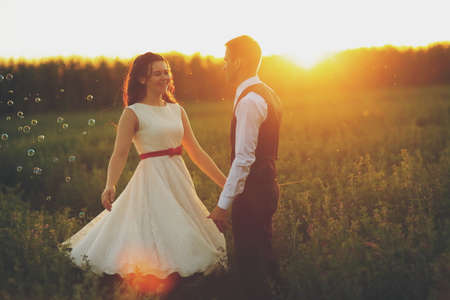 Happy bride and groom in the light of car headlights. Wedding. Happy love concept. High quality photo