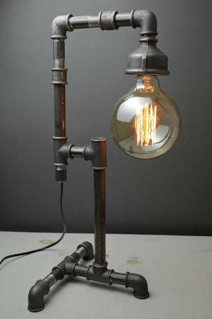 Retro lamp made of metal water pipes with an Edison lamp on a gray background. The concept is a good idea. High quality photo