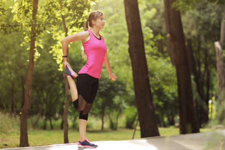 The young woman is engaged in sports fitness in nature forest Healthy fit living. Motivation healthy fit living. Running shoe. Beautiful sunlight. Woman warming up before running Stock fotó