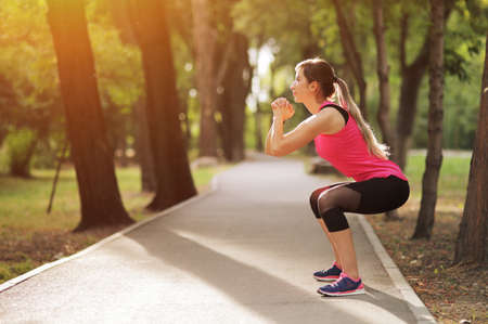 The young woman is engaged in sports fitness in nature forest Healthy fit living. Motivation healthy fit living. Running shoe. Beautiful sunlight. Woman warming up before running. Squats