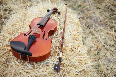 One violin and bow placed on a pile of straw in the field. Music Violin training. Fiddlestick, performing. Concept, baroque. Musical, fiddle. Zdjęcie Seryjne