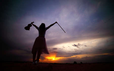 Romantic young woman with loose hair, holding a violin in her hand in a field at sunset after harvest. Square sheaves of hay in the field. Violin training Reklamní fotografie