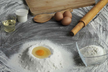 Broken chicken egg in a pile of flour, olive oil, milk, kitchen tool on gray table background. Products for baking bakery products. Cutting board, rolling pin, flour sieve, wooden spoon. bread or cake