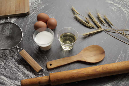 Chicken egg, flour, olive oil, milk, wheat ears, kitchen tool on gray table background. Products for baking bakery products. Cutting board, rolling pin, flour sieve, wooden spoon. For bread or cake Zdjęcie Seryjne