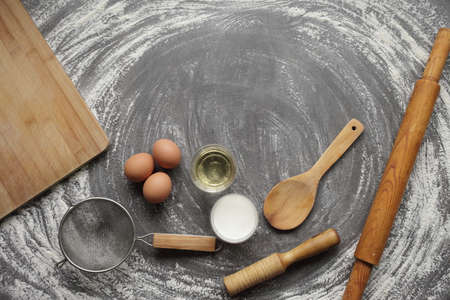Chicken egg, flour, olive oil, milk, kitchen tool on gray table background. Products for baking bakery products. Cutting board, rolling pin, flour sieve, wooden spoon. For bread or cake
