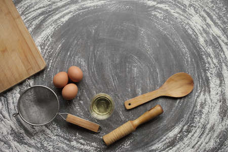 Chicken egg, flour, olive oil, kitchen tool on gray table background. Products for baking bakery products. Cutting board, rolling pin, flour sieve, wooden spoon. For bread or cake