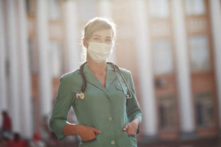Confident female doctor or nurse wearing a face protective mask. Safety measures against the coronavirus. Prevention Covid-19 healthcare concept. Stethoscope over the neck. Woman, girl.