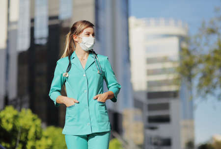 Female doctor, a nurse wearing a protective face mask in the city. Skyscraper, sky. Safety measures against the coronavirus. Prevention Covid-19 healthcare concept. Stethoscope. Woman, girl. 免版税图像