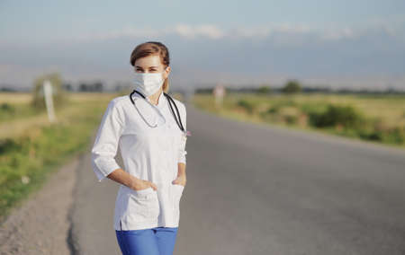 Female doctor or nurse wearing a protective face mask next to a rural road. Safety measures against the coronavirus. Prevention Covid-19 healthcare concept. Stethoscope over the neck. Woman, girl.