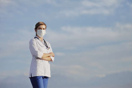 Female doctor, a nurse wearing a protective face mask against blue sky with clouds. Safety measures against the coronavirus. Prevention Covid-19 healthcare concept. Stethoscope. Woman, girl.