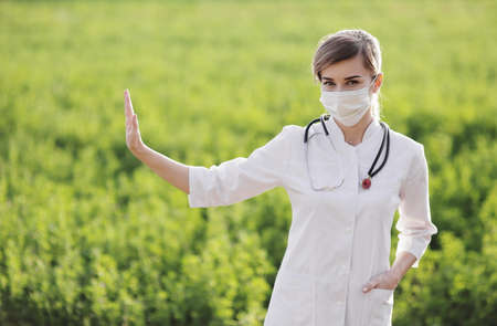 A Female doctor in a medical face mask showing a stop pandemic gesture. Confident female doctor or nurse wearing a face protective mask on green grass background. Coronavirus Covid19. Girl, woman