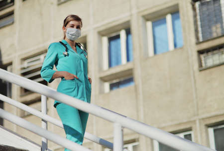 Female doctor or nurse in a protective face mask walking up the stairs. Safety measures against the coronavirus. Prevention Covid-19 healthcare concept. Stethoscope over the neck. Woman, girl.