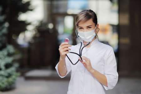 A woman doctor in a face protective medical mask with a stethoscope ready to check lungs. Safety measures against the coronavirus. Prevention Covid-19 healthcare concept. Girl. 免版税图像