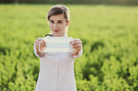Young woman doctor or nurse showing medical face mask close up. On green grass background. Prevention Covid-19 healthcare concept. Stethoscope over the neck. Female, girl. 免版税图像