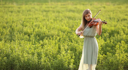 Romantic woman with loose hair playing the violin. Sunset light in nature. Violin training
