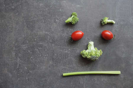 Displeased emoticon of fresh vegetables cherry tomatoes broccoli and celery. High quality photo Reklamní fotografie