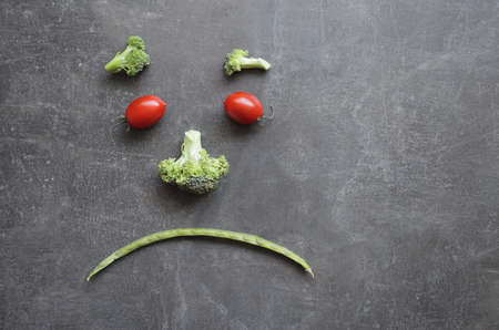 Sad emoticon made from fresh vegetables, cherry tomatoes, broccoli and green beans. High quality photo Reklamní fotografie