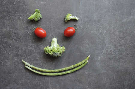 Smiling emoticon of fresh vegetables cherry tomatoes broccoli and green beans. High quality photo Reklamní fotografie